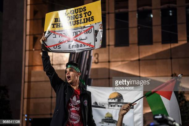 A man holds a placard reading 'AlQuds belongs to the muslims' as he shouts slogans next to a protestor holding a Palestinian flag while they take...