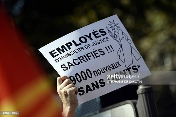 A man holds a placard reading 'Bailiffs' employees sacrificed ' during a protest of dozens of bailiffs against a government planned reform of the...