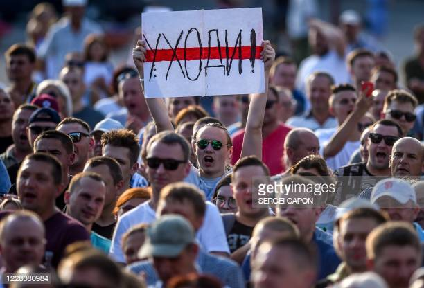 "Man holds a placard reading ""Go away"" as he chants slogans during an opposition rally in Salyhorsk some 150 km south of Minsk, on August 17 after..."