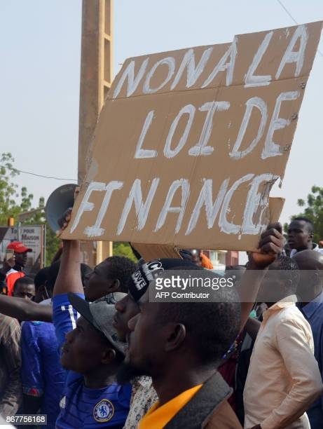 A man holds a placard reading 'No to the finance law' during a demonstration against the 2018 Finance law on October 29 in Niamey Over a thousand...