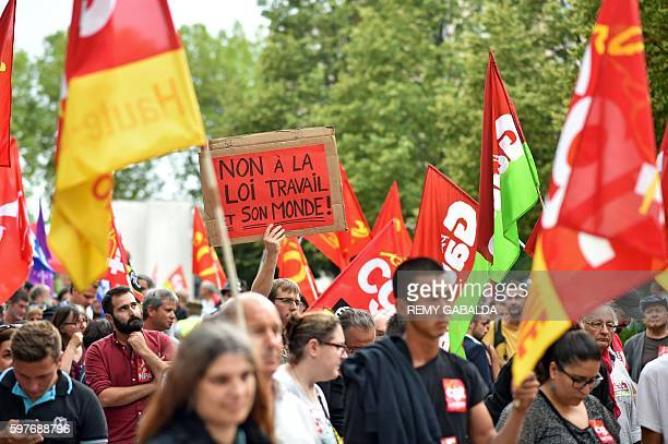 A man holds a placard reading No to the labour law and its world as he marches during a protest against the Labour law reform organised by French...