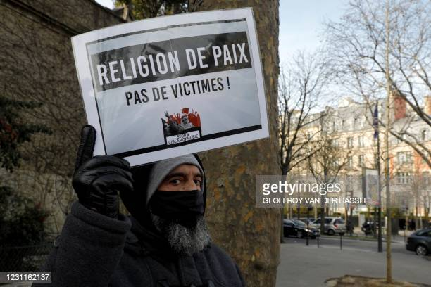 """Man holds a placard reading """"religion of peace"""" as protesters demonstrate against a bill dubbed as """"anti-separatism"""", in Paris on February 14, 2021...."""