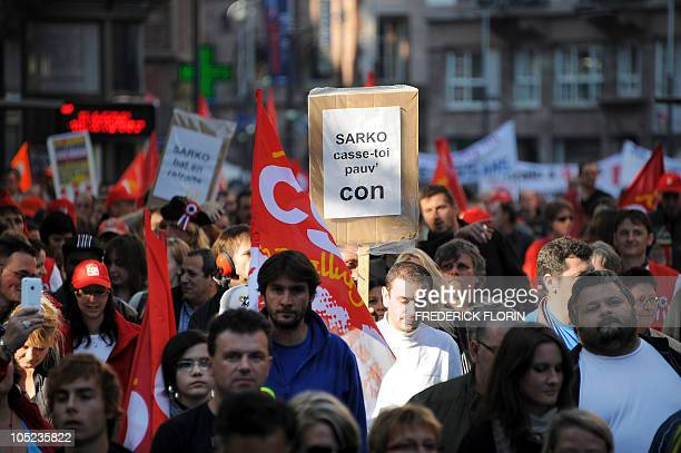 A man holds a placard reading ' Sarkozy leave asshole' as French workers demonstrate on October 12 2010 in Strasbourg eastern France to protest...