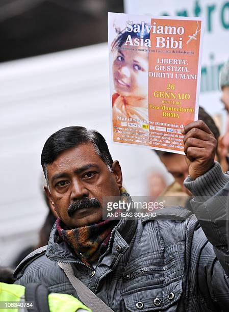 """Man holds a placard reading """"Save Asia Bibi"""" during a demonstration in front of the Italian Parliament in central Rome on January 26, 2011 against..."""