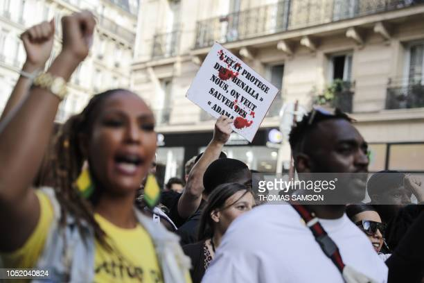 A man holds a placard reading 'The State protects some 'Benalla' we want to save some 'Adama'' during a demonstration in Paris on October 13 2018 in...