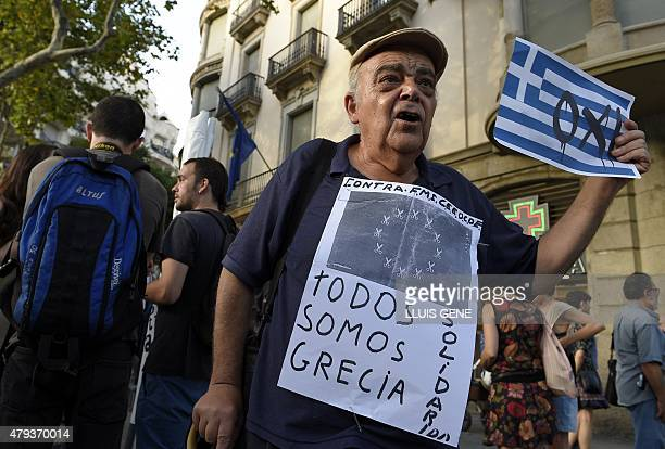 A man holds a placard reading 'We all are Greece Solidarity' and holds a Greek flag with a 'NO' on it as he protests in front of the European...
