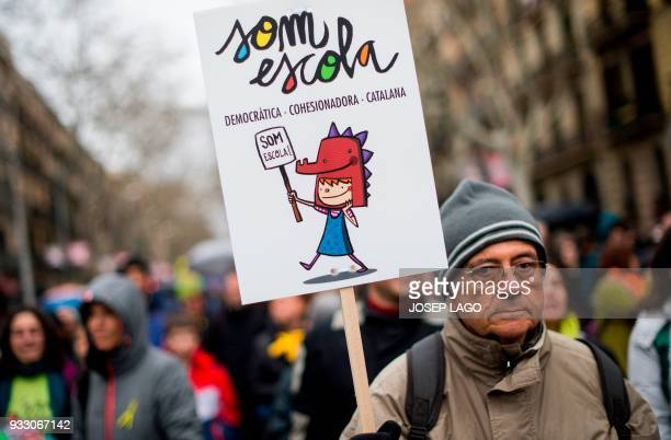 A man holds a placard reading 'We are school democratic cohesive and catalan' during a demonstration titled 'The democratic and cohesive school is...
