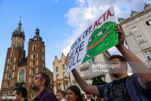 A man holds a placard saying 'F#uck off ACTA we are full ' during a protest against the implementation of ACTA 2 in European Union On June 20th The...