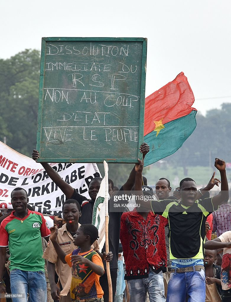 A man holds a placard that reads, 'Immediate dissolution to the RSP (Presidential Security Regiment), no to the coup d'etat, long live the people' during a protest in the city of Hounde, capital of Tuy Province, in east central Burkina Faso, on September 19, 2015. The protest comes several days after a military coup on September 16, by General Gilbert Diendere, an aide to ousted president Blaise Compaore and members of Compaore's powerful Presidential Security Regiment (RSP) burst into the cabinet meeting room snatching the country's interim president Michel Kafando and Prime Minister Isaac Zida, and two ministers (Augustin Loada and Rene Bagoro). Compaore was toppled October 2014 and fled into exile in Ivory Coast after a popular uprising triggered by his attempt to extend his 27-year rule.