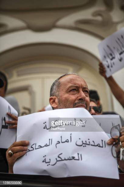 Man holds a placard that reads in Arabic release Yassine Ayari, no to the military trials of civilians, during a demonstration held in Tunis,...