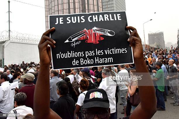 A man holds a placard that reads 'Je suis Charlie n'oublions pas les victimes de Boko Haram' as people gather outside the French embassy in Abidjan...