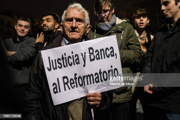 """Man holds a placard that reads """"Justice and banking to the reformatory"""", protesting in front of Supreme Court against mortgage taxes. Supreme Court..."""