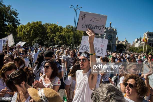 A man holds a placard that reads 'Let's talk' during a protest demanding dialogue between Spanish Government and Catalonia ahead of a possible...