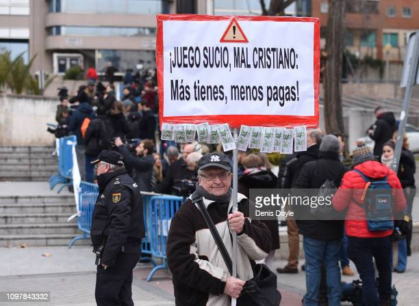 A man holds a placard which reads 'Cristiano Ronaldo bad sportsman the more you have the less you pay' outside the Audiencia Provincial de Madrid...