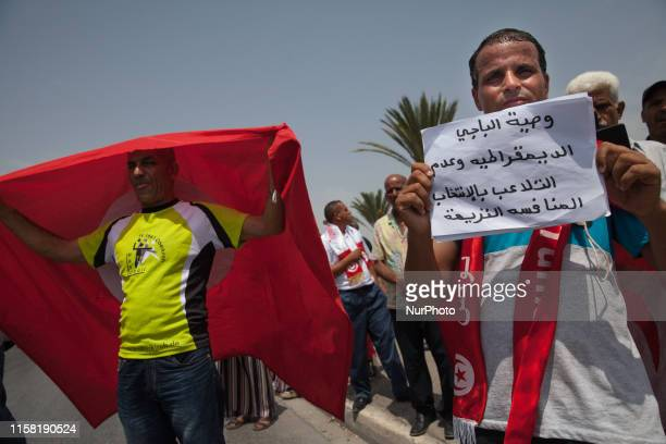 Man holds a placard which reads in Arabic 'The will of Beji Caid Essebsi: democracy and non-manipulation of the elections. Fair competition', as he...