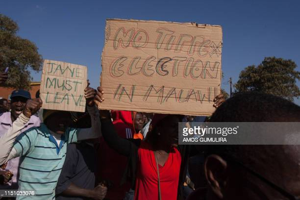 Man holds a placard while thousands of opposition parties supporters participate in a protest march in the capital Lilongwe on June 20 to force...