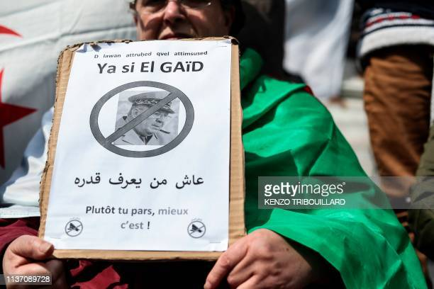 A man holds a placard with a portrait of Algeria's Chief of Staff General Ahmed Gaid Salah with the words reading The soonest you leave the better is...
