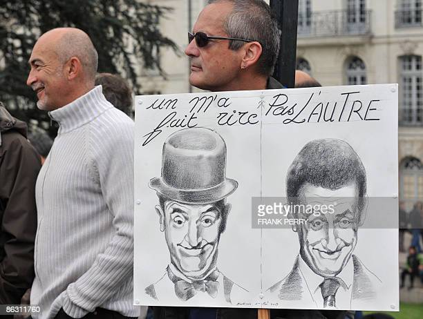 A man holds a placard with drawings of US actor Laurel Hardy and French President Nicolas Sarkozy and reading 'one made me laugh not the other one'...
