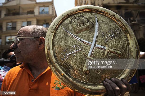 Man holds a plaque of the Muslim Brotherhood emblem which was removed from the party's burnt out headquarters in the Moqattam district of Cairo, on...