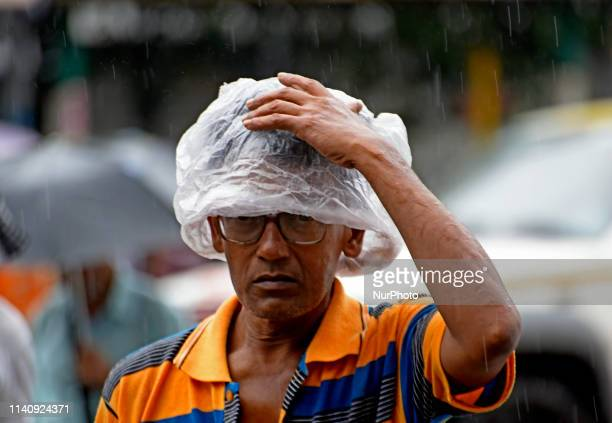 A man holds a plastic during heavy rainfall in Kolkata on 03 May 2019 as the cyclonic storm Fani hits the coastal places of Orissa and West Bengal on...