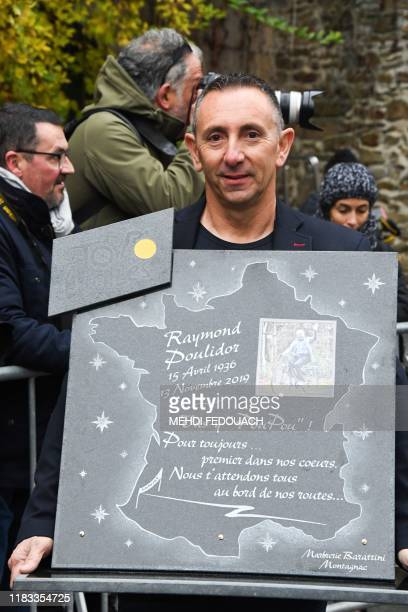 A man holds a plate to pay tribute to Raymond Poulidor as people attend the funerals of French cyclist in SaintLeonarddeNoblat on November 19 2019...