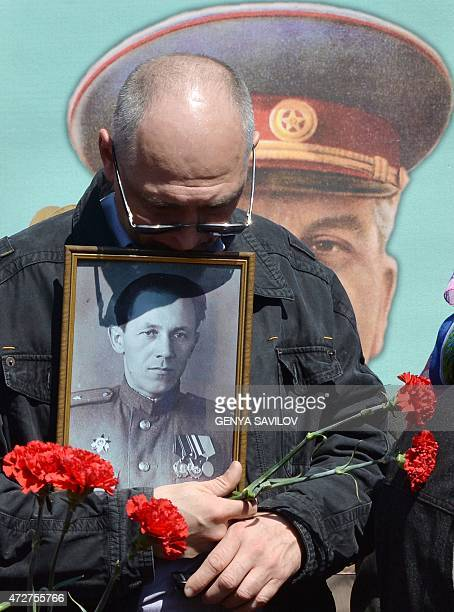 A man holds a portrait of a relative in front of a portrait of Soviet dictator Josef Stalin at the Memorial of the unknown soldier in Kiev on May 9...
