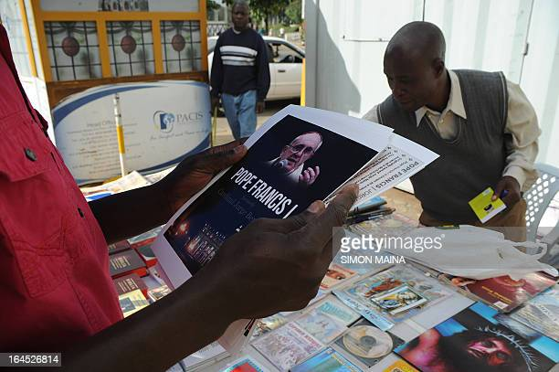 A man holds a portrait of Pope Francis on sale outside the Holy Basilica on March 24 2013 in Nairobi Pope Francis kicked off his Palm Sunday ceremony...