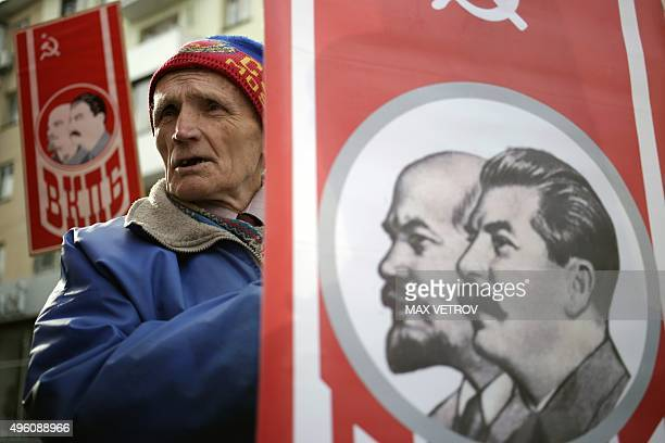 A man holds a portrait of Soviet Union founder Vladimir Lenin and Soviet leader Joseph Stalin during a rally to mark the 98th anniversary of Russia's...