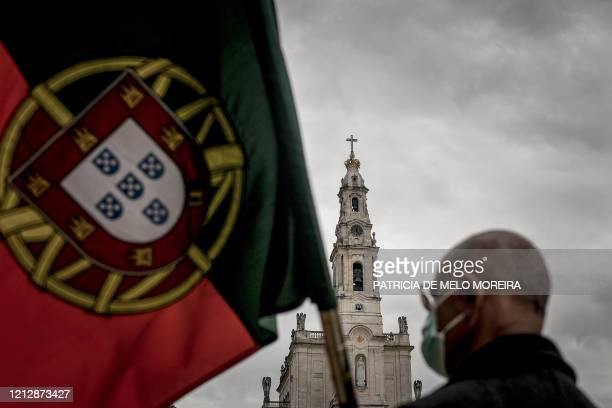 Man holds a Portuguese flag during the 103rd anniversary of the apparitions of Our Lady of Fatima at the Fatima shrine in central Portugal on May 13,...