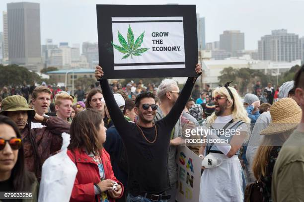 A man holds a poster as a crowd of about two thousand people march through the city centre to call for the complete legalisation of marijuana in Cape...
