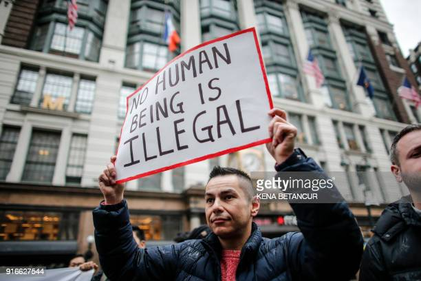 A man holds a poster as he attends a protest in support of immigration in herald Square on February 10 2018 in New York / AFP PHOTO / KENA BETANCUR