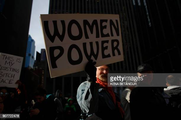 TOPSHOT A man holds a poster as he attends the Womens March on New York City on January 20 2018 in New York City / AFP PHOTO / KENA BETANCUR