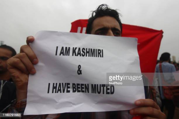 A man holds a poster as he takes part in a protest against the scrapping of Article 370 in Jammu and Kashmir in Mumbai India on 07 August 2019...