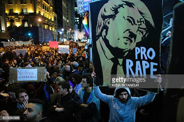TOPSHOT A man holds a poster as she takes part in a protest against Presidentelect Donald Trump in New York City on November 9 2016