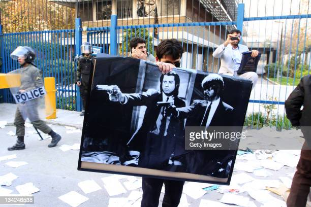 A man holds a poster featuring American actors John Travolta and Samuel L Jackson in a scene from the film 'Pulp Fiction' following a break in at the...