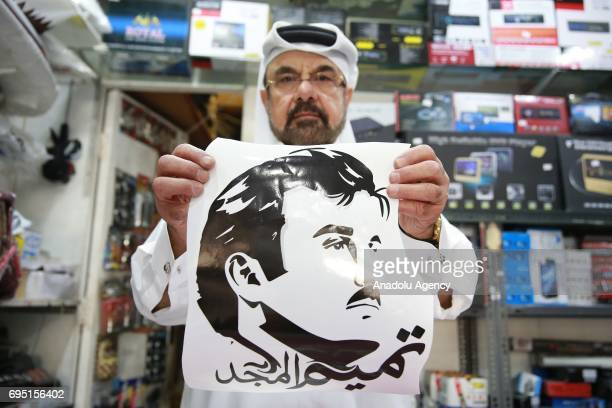 A man holds a poster of Emir of Qatar Sheikh Tamim bin Hamad Al Thani at a printing house in Doha Qatar on June 12 2017 People in Qatar hang posters...