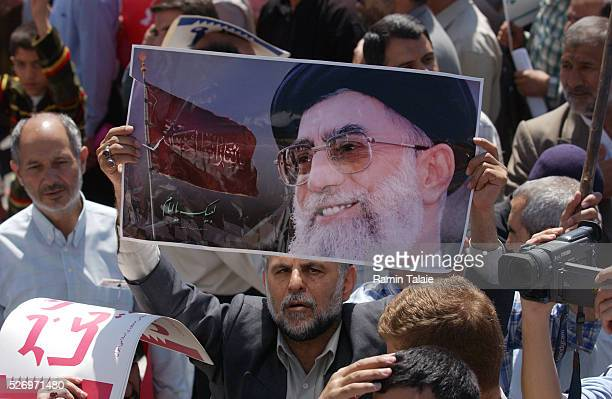 A man holds a poster of Iran Supreme Leader Ayatollah Khamenie Tens of thousands of Iranians rallied in Enghelab Square to protest US and British...