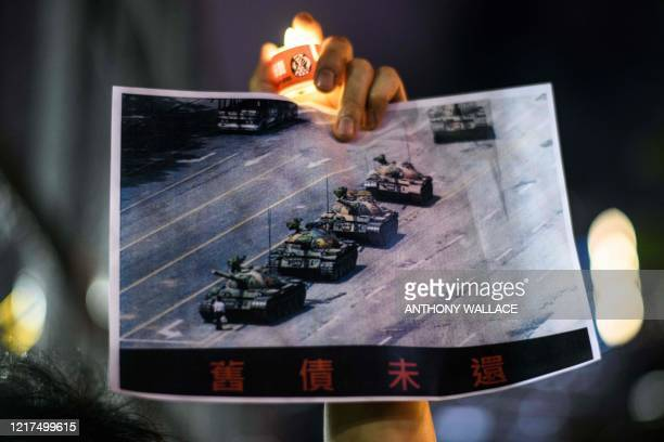Man holds a poster of the famous 'Tank Man' standing in front of Chinese military tanks at Tiananmen Square in Beijing on June 5 during a candlelit...