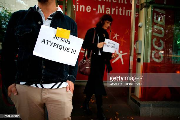 A man holds a poster reading 'I am atypical' outside the building of the departement council of the SeineMaritime during a protest after the...