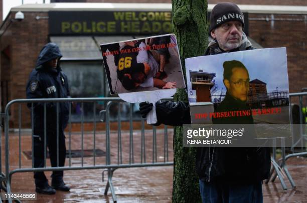 A man holds a poster showing an image of Eric Garner outside police headquarters as a disciplinary hearing takes place for officer Daniel Pantaleo...