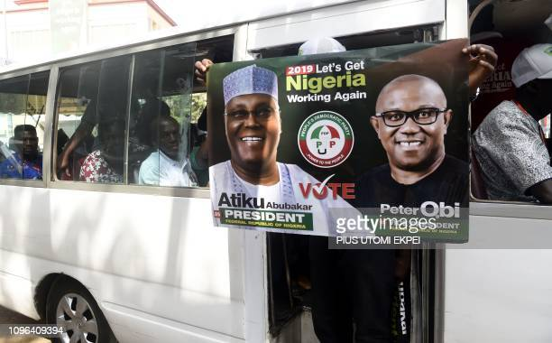 A man holds a poster showing main opposition PDP party presidential candidate Atiku Abubakar and his running mate for vice president Peter Obi as...