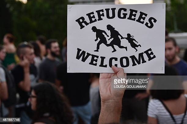 A man holds a poster welcoming refugees during a rally in support of migrants and refugees as part of the European Day of Action in Athens on...
