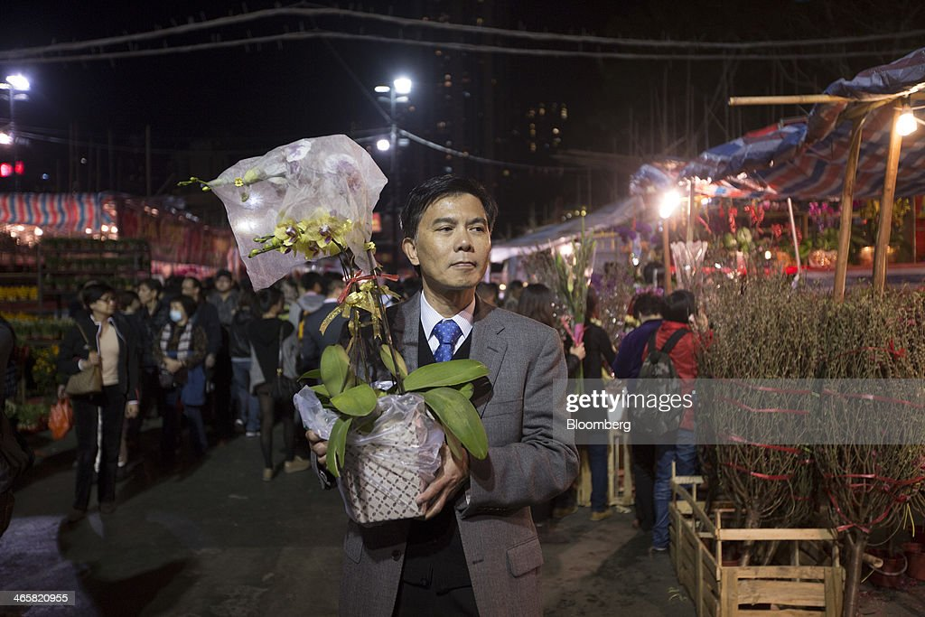 A man holds a pot of orchids at the Lunar New Year fair at Victoria Park in Hong Kong, China, on Wednesday, Jan. 29, 2014. The citys financial markets will close early on Jan. 30 for the Chinese New Year holidays and resume trading on Feb. 4, while those in the mainland will be shut from tomorrow through Feb. 6. Photographer: Brent Lewin/Bloomberg via Getty Images
