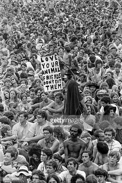 A man holds a provegetarian poster amongst the crowd at the Woodstock Music Art Fair Bethel NY August 15 1969