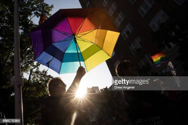 A man holds a rainbow umbrella during a Flag Day 'Raise the Rainbow' march June 14 2017 in New York City The event honored LGBT rainbow flag creator...