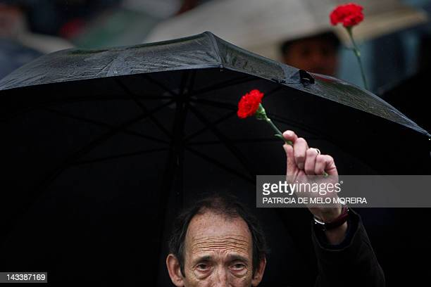 A man holds a red carnation a symbol of the 1974 Portuguese revolution as he march in downtown Lisbon on April 25 during a demonstration to celebrate...