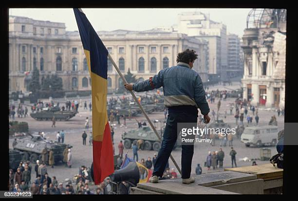 Man holds a Romanian flag with the Communist symbol torn from its center on a balcony overlooking the tanks, soldiers, and citizens filling Palace...