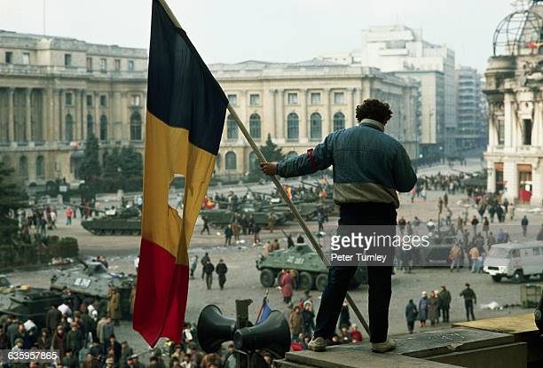 A man holds a Romanian flag with the Communist symbol torn from its center on a balcony overlooking the tanks soldiers and citizens filling Palace...