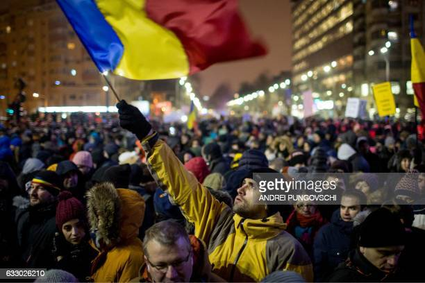 TOPSHOT A man holds a Romanian national flag during a demonstration to protest against controversial decrees to pardon corrupt politicians and...