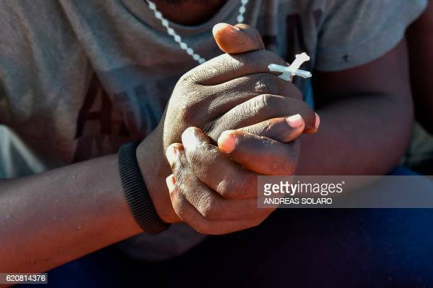 A man holds a rosary as he sit aboard the Topaz Responder ship run by Maltese NGO Moas and the Italian Red Cross during a rescue operation of...